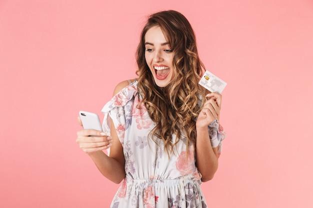 Mulher bonita em vestido segurando smartphone e cartão de crédito, isolado em rosa
