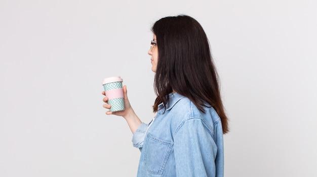 Mulher bonita em vista de perfil pensando, imaginando ou sonhando acordada e segurando um café para viagem