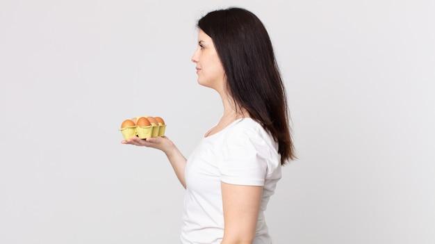 Mulher bonita em vista de perfil pensando, imaginando ou sonhando acordada e segurando uma caixa de ovos