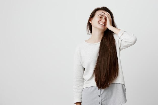 Mulher bonita emocional, com longos cabelos escuros, vestido casualmente, mantém a mão na cabeça, sorri com alegria, ri