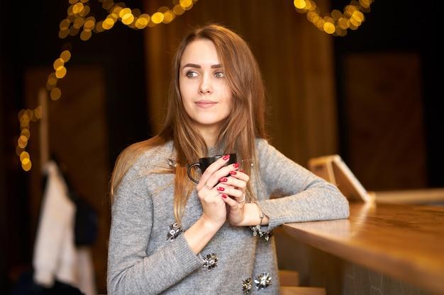 Mulher bonita encantadora atraente, com cabelos longos e sorriso amigável localização no café e segurando a xícara de café preta.