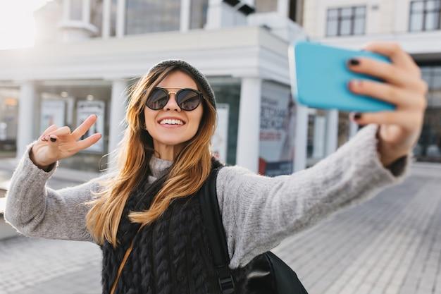 Mulher bonita encantadora elegante em óculos de sol modernos, suéter de inverno quente fazendo selfie retrato na rua no centro da cidade. aparência elegante, se divertindo, expressando emoções positivas brilhantes.