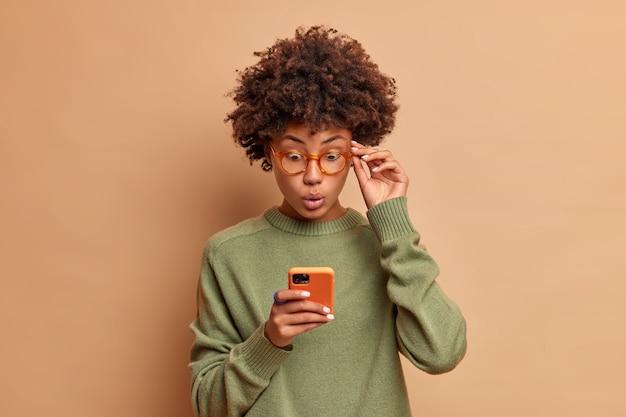 Mulher bonita encaracolada sem palavras impressionada olha fixamente para carrinhos de smartphone com olhos esbugalhados mantém a mão na borda dos óculos usa um macacão casual expressão chocada lê notícias