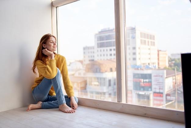 Mulher bonita encontra-se no parapeito da janela estilo de vida. foto de alta qualidade
