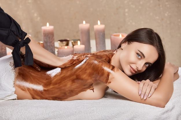 Mulher bonita enquanto faz massagem de chocolate em salão de beleza com terapeuta profissional