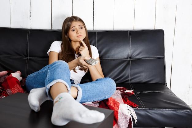 Mulher bonita entediada assistindo tv, sentado no sofá em casa.