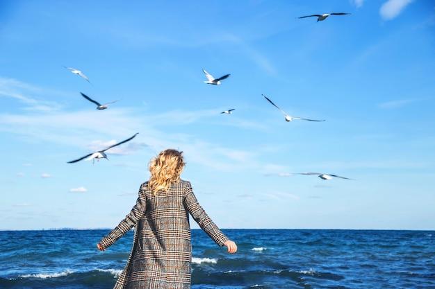 Mulher bonita entra no outono e pratica a atenção plena à beira-mar com gaivotas.