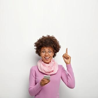 Mulher bonita envia mensagens de texto via celular, navega na página da internet online, aponta para cima com o dedo indicador
