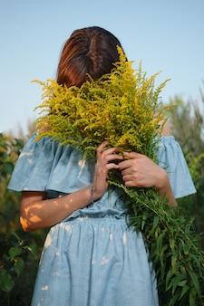 Mulher bonita, escondendo o rosto em flores do campo