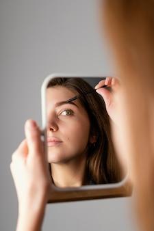 Mulher bonita escovando as sobrancelhas enquanto se olha no espelho após o tratamento