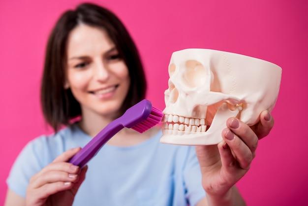 Mulher bonita escovando os dentes de um crânio artificial com uma escova de dentes grande