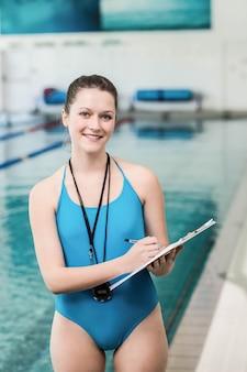 Mulher bonita, escrevendo na área de transferência na piscina