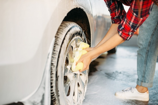 Mulher bonita esfregando a roda do veículo com espuma