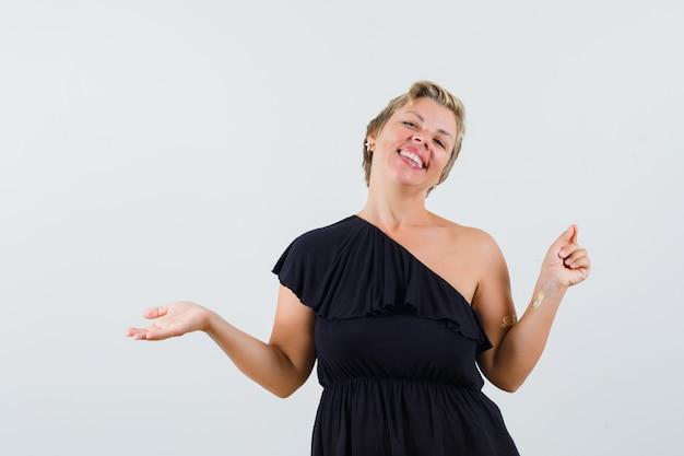Mulher bonita espalhando a palma da mão aberta de lado, mostrando algo na blusa preta e parecendo feliz.