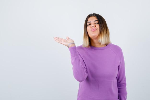 Mulher bonita espalhando a palma da mão de lado, fazendo beicinho com os lábios no suéter roxo e olhando em paz, vista frontal.