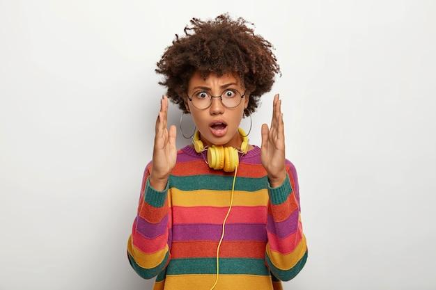 Mulher bonita espantada gesticula com as duas mãos, apresenta algo incomumente grande, mantém a boca aberta de admiração, usa suéter listrado colorido, fones de ouvido no pescoço