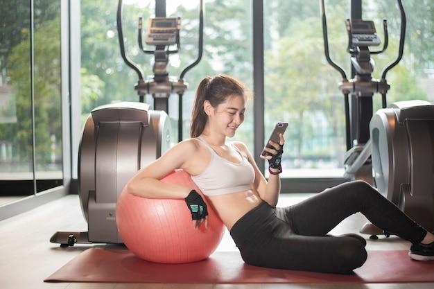 Mulher bonita esporte asiático está jogando telefone inteligente no ginásio