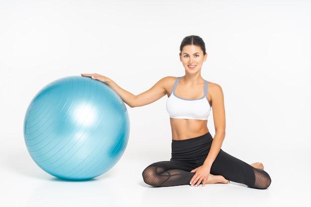 Mulher bonita esporte fazendo alongamento exercícios de fitness na bola.