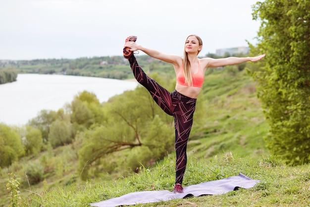 Mulher bonita esportes está esticando a perna enquanto faz exercícios de esporte na margem do rio no verão