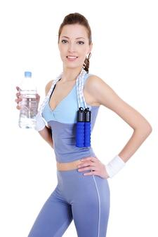Mulher bonita esportiva com garrafa de água na mão