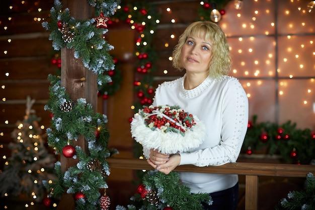 Mulher bonita está de pé com buquê decorativo de ano novo nas mãos dela