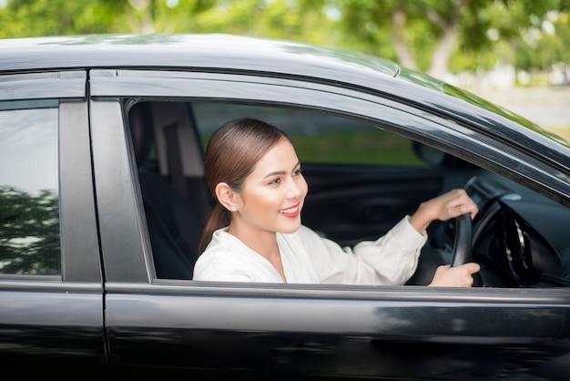Mulher bonita está dirigindo seu carro