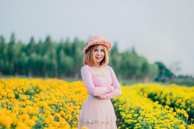 Mulher bonita está em um jardim de flores e está lá olhando na frente.