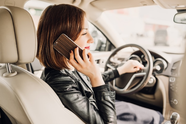 Mulher bonita está falando no telefone celular e sorrindo enquanto está sentado no carro