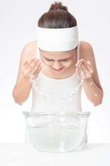 Mulher bonita está lavando o rosto no fundo branco