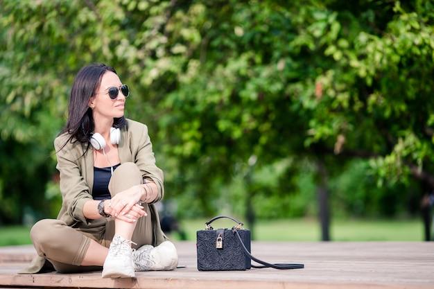 Mulher bonita está lendo a mensagem de texto no celular enquanto está sentado no parque.
