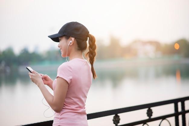 Mulher bonita está ouvindo música no parque