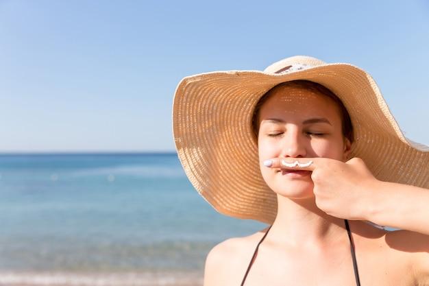 Mulher bonita está posando com bigode desenhado com protetor solar no dedo debaixo do nariz para o fundo do mar.