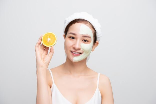 Mulher bonita está recebendo máscara de argila facial e segurando pedaços de laranja em fundo branco. conceito de beleza, cuidados com o corpo e spa