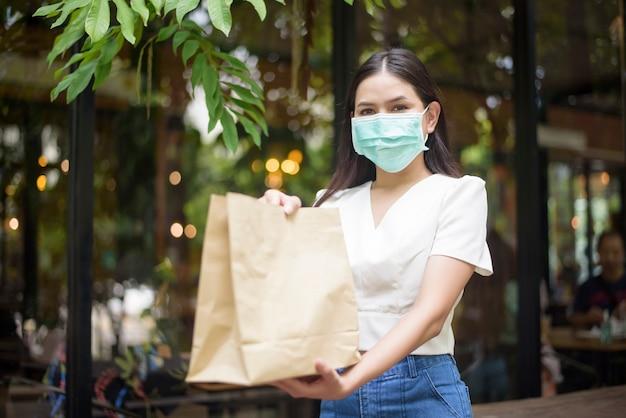 Mulher bonita está recebendo sacola de compras em casa