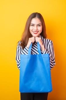 Mulher bonita está segurando o saco de pano azul