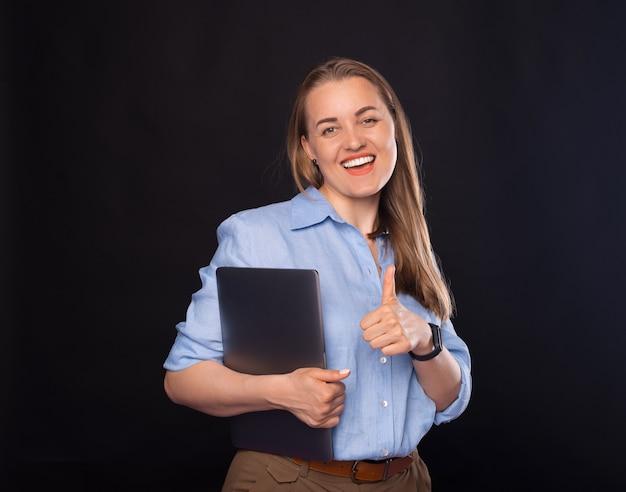 Mulher bonita está segurando seu laptop e mostrando como um gesto.