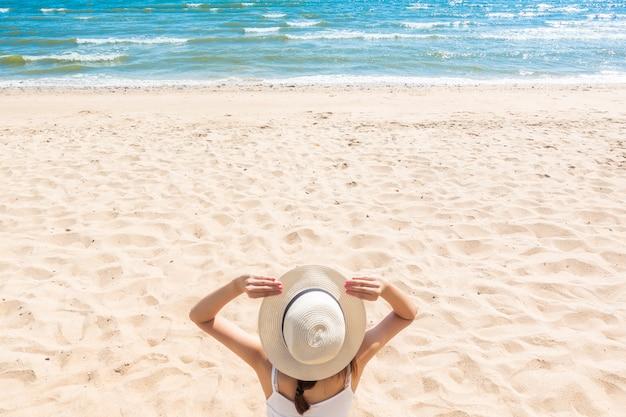 Mulher bonita está sentada na praia
