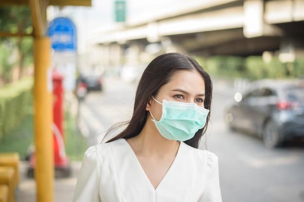 Mulher bonita está usando máscara facial no ponto de ônibus