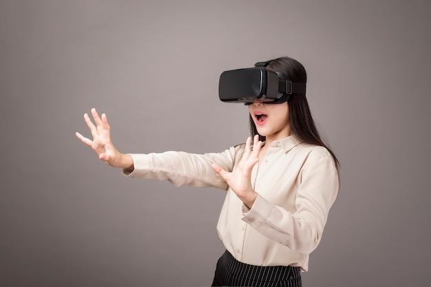 Mulher bonita está usando realidade virtual em cinza