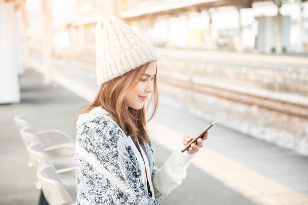 Mulher bonita está usando telefone inteligente na plataforma ferroviária