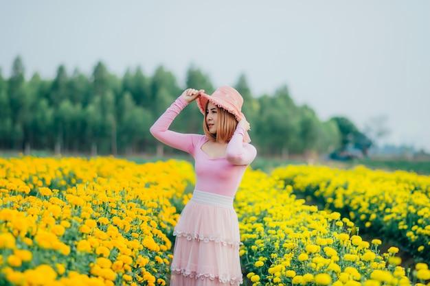 Mulher bonita estava em um jardim de flores e estava em pé segurando seu chapéu.