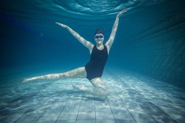 Mulher bonita, estendendo-se debaixo d'água na piscina
