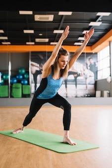 Mulher bonita, esticando o braço durante a ioga