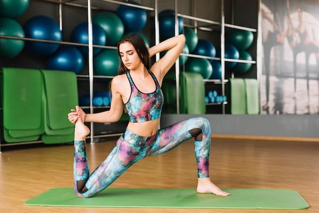 Mulher bonita, esticando os músculos do corpo no tapete de ioga verde