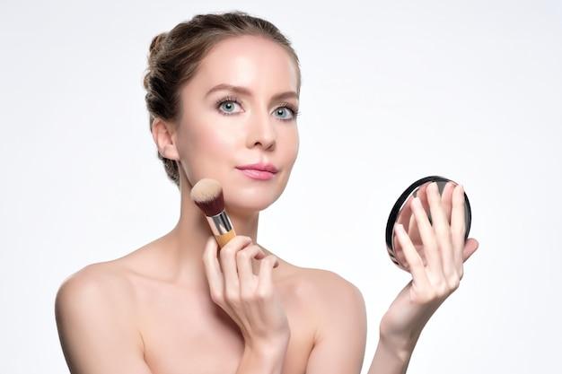 Mulher bonita europeia aplicando pó de pele para uma aparência perfeita.