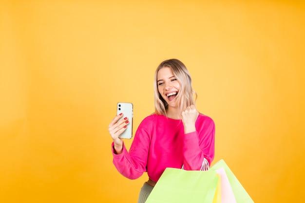 Mulher bonita europeia com blusa rosa na parede amarela Foto gratuita