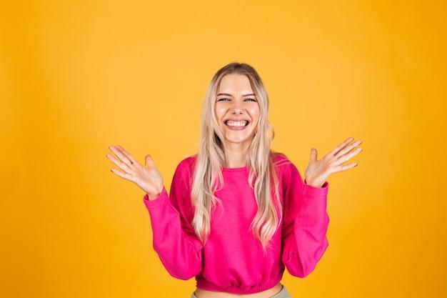 Mulher bonita europeia com blusa rosa na parede amarela