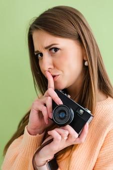 Mulher bonita europeia com câmera fotográfica em mãos positivas mostra sinal de shh com o dedo, gesto de silêncio