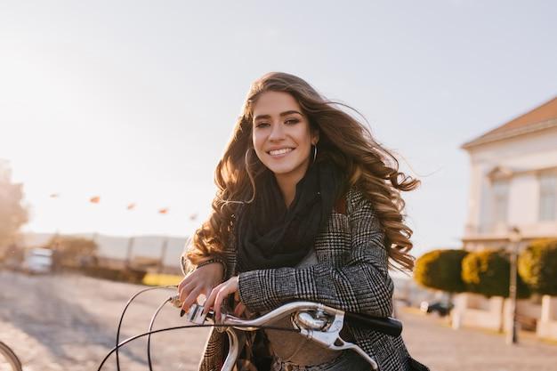 Mulher bonita europeia com lindos cabelos cacheados posando em um dia frio de outono na praça da cidade