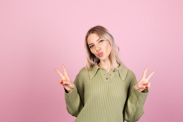 Mulher bonita europeia com suéter casual na parede rosa
